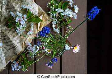 Small bouquet of spring field flowers in a glass jar on wooden rustic background, top view. Selective focus