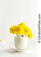 Small bouquet of yellow spring flowers in white cup. Closeup view