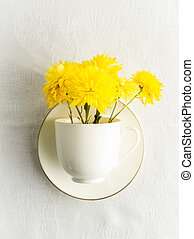 Small bouquet of yellow spring flowers in white cup, saucer on white tablecloth, closeup view