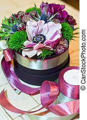 Small bouquet with pink flower in a box with ribbons