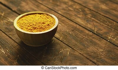 Small bowl of orange turmeric spice - Closeup shot of small...