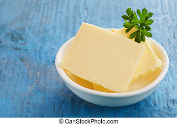 Small bowl with slices of fresh yellow butter