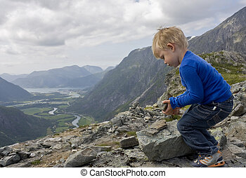 Small boy (3 years old) building a cairn on top of Litjfjellet. ?ndalsnes in the background. Rauma, Norway.