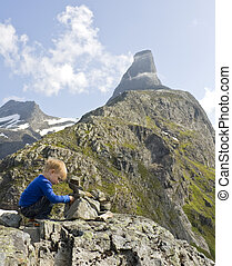 Small boy (3 years old) building a cairn on top of Litjfjellet. Romsdalshorn in the background. Rauma, Norway.