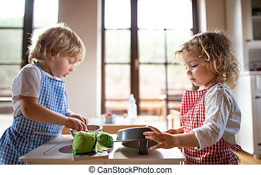 Small boy and girl with apron playing indoors with toy kitchen at home.