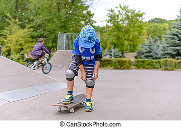 Small boy at the skate park in summer