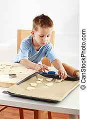 Small boy baking cookies