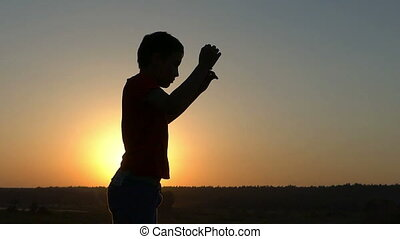 Small Boy Does Physical Exercises in Profile at Sunset in Slow Motion