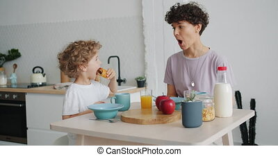 Small boy feeding mother with croissant then drinking during...