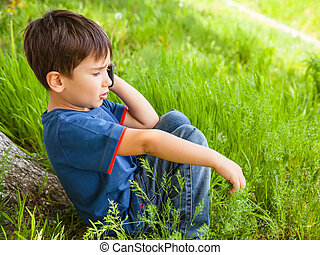 boy in green grass talking on cell phone