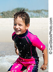 small boy in his diving suit smiling at the beach