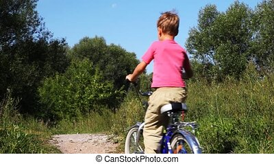 small boy in pink t-shirt on blue bicycle go on footpath in park