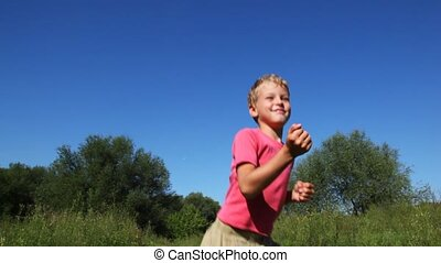 small boy in pink t-shirt runs on place and smile in park in summer