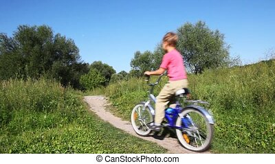 small boy in pink vest goes forward on blue bicycle in park in summer
