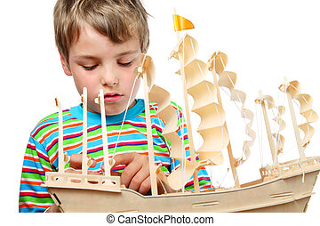 Small boy in striped shirt work with zeal on artificial ship...