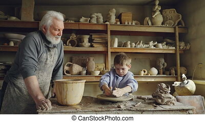 Small boy is molding clayware in his grandfathers's studio while his caring senior grandpa is standing near him and watching him with love. Family traditions concept.