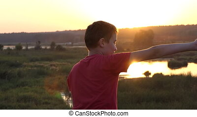Small Boy Laughs And Plays Kung-Fu on a Lake Bank With Bulrush at Sunset