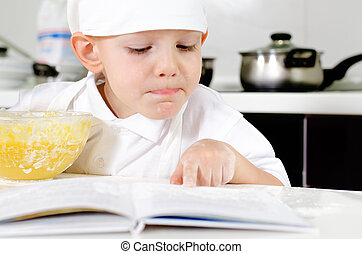 Small boy learning to cook checking his mixture in the mixing bowl against the ingredients in the recipe book