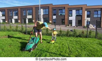 Small boy mows grass just like his dad. Father and son care...