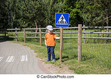 Small boy on road. The concept of studying the rules of the road.