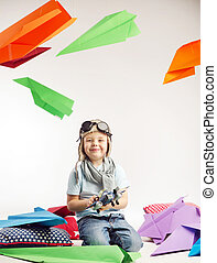Small boy playing toy plane - Small cute boy playing toy...