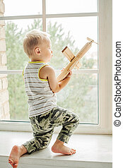 Small boy playing with wooden plane toy at home. Child dreaming on flight