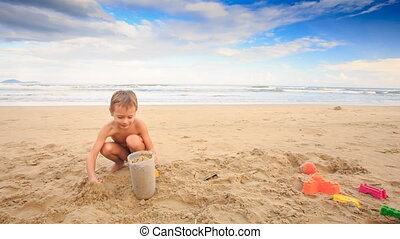 Small Boy Plays with Wet Sand Fills