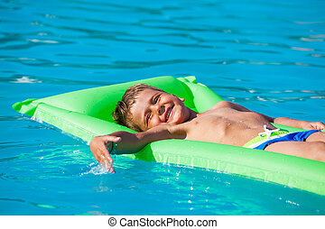 Small boy relaxing on green inflatable mattress