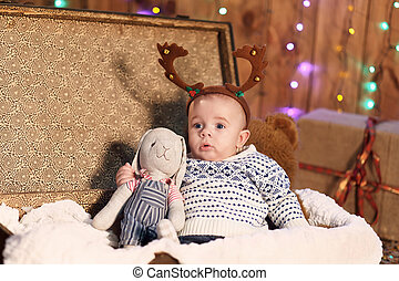 small boy sits in a suitcase with a toy in the room with Christmas decorations