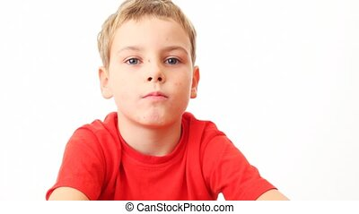 small boy sits, looks, blinks his eyes on white background