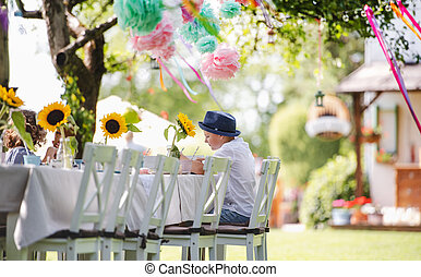 Small boy sitting at the table outdoors on garden party in summer, eating.