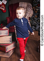 small boy standing near books at christmas time