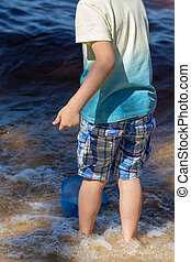 Small boy stands with a fishing net directly in the sea