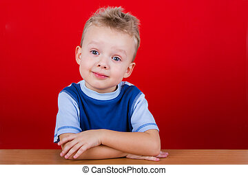 Small boy in blue T-shirt, sitting at the table. On a red...