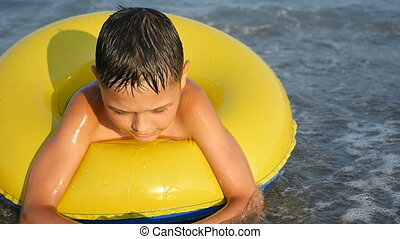 Small boy swims in a yellow inflatable ring in the sea in summer in slow motion