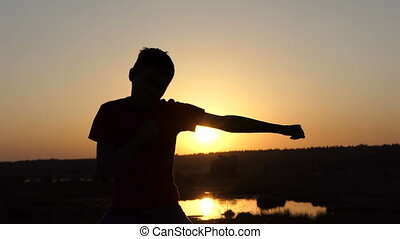 Small Boy Trains Boxing Blows on a Lake Bank at Sunset in Autumn in Slo-Mo