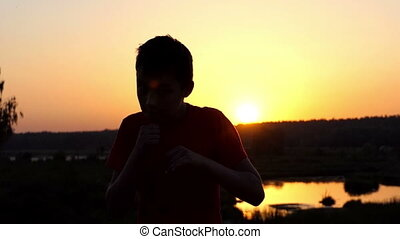 Small Boy Trains Boxing Hooks on a Lake Bank at Sunset in Autumn in Slo-Mo