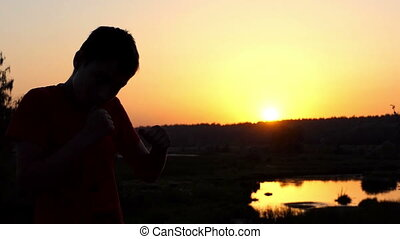 Small Boy Trains Boxing Uppercuts on a Lake Bank at Sunset in Autumn in Slo-Mo