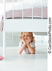 Small boy under bed - Happy small boy lying under bed in...