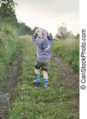 Small boy walking on the forest path