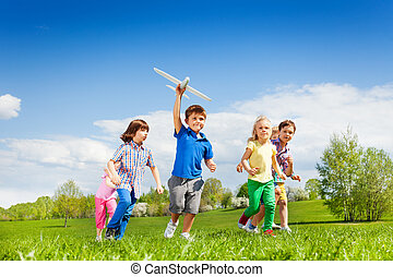 Small boy with airplane toy and friends running