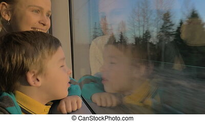 Small boy with mother sitting against window in their rail train place and watching outside