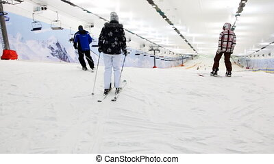 small boy with snowboard starts to go down in sport center