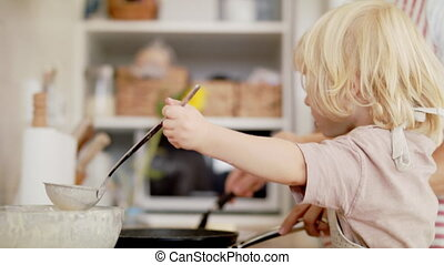 Small boy with unrecognizable mother indoors in kitchen, ...