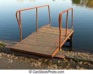 Small bridge on the autumn lake