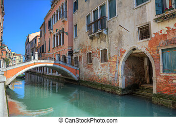 Small bridge over canal and old houses in Venice.
