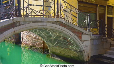 Small bridge over canal in Venice with moving sun...