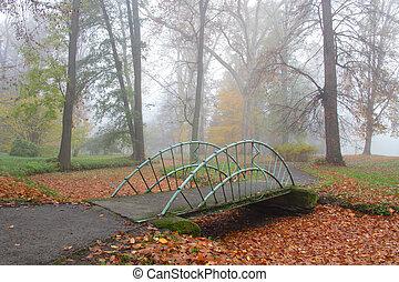 Small bridge over dry creek in misty park