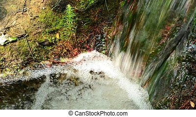 Small brook or river with tiny waterfall with fast flowing...