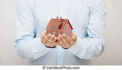 Small brown toy house in hands
